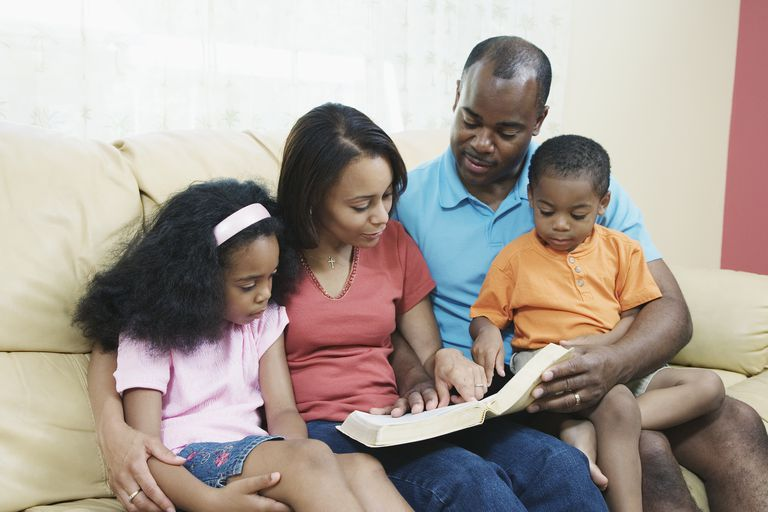 Parents with children (4-7) on sofa, reading bible, smiling