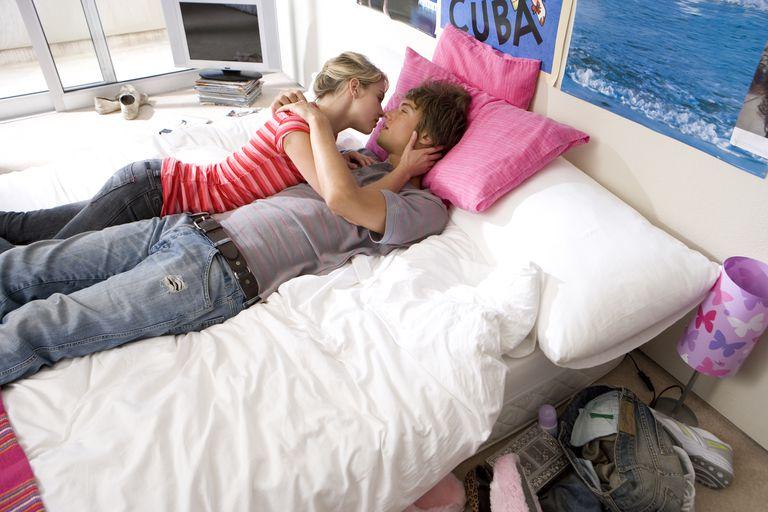 Pareja adolescente besándose en la cama