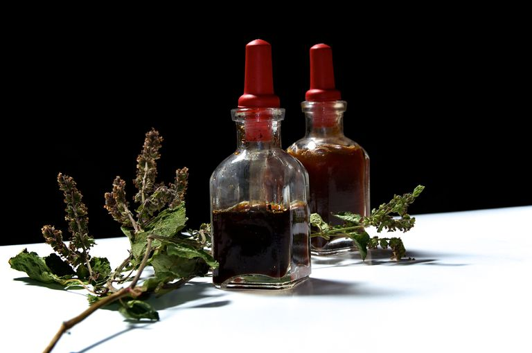 Two glass bottles with herbal extracts and dried patchouli flowers
