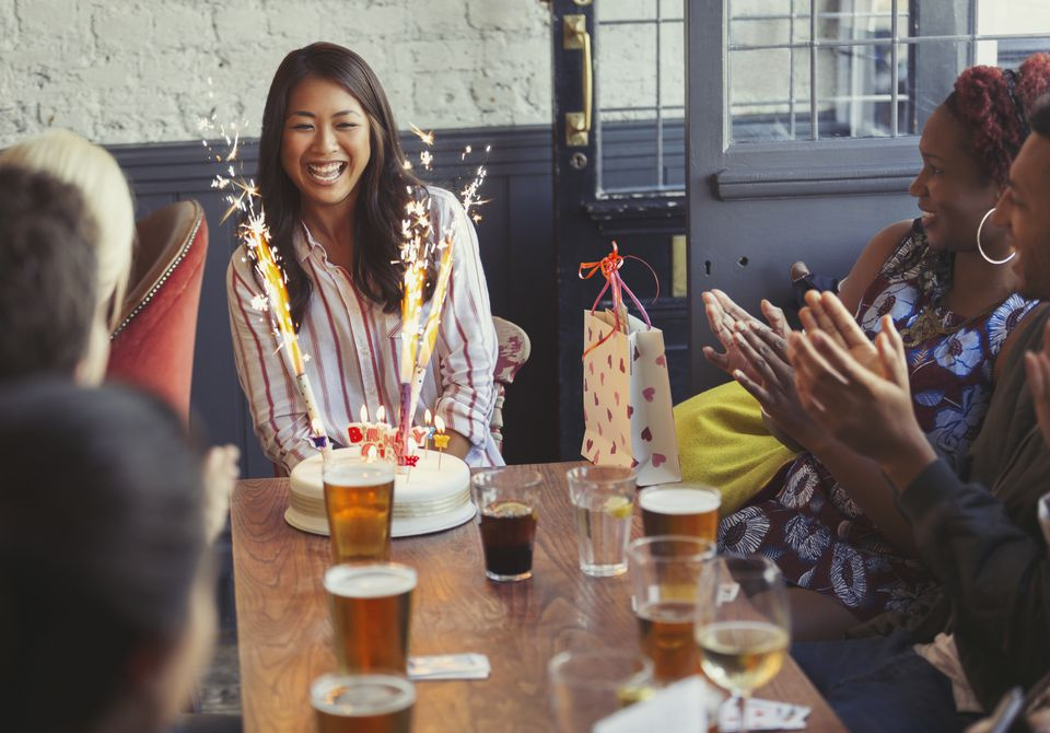 Friends clapping for happy woman with fireworks birthday cake at restaurant table