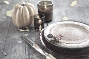 pumpkin pie next to small pumpkin and candles