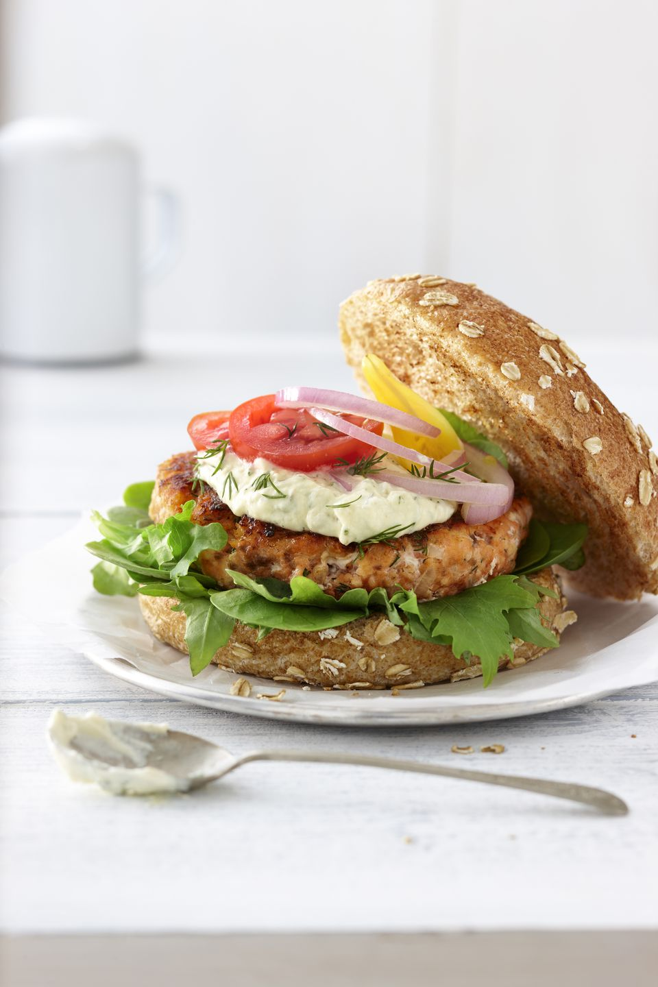 Salmon burger on whole wheat bun with lettuce, red onion, red tomatoes, yellow tomatoes, sauce, and fresh dill