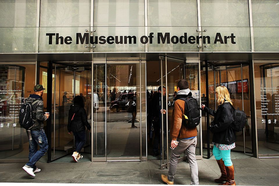 People walk into the Museum of Modern Art (MoMA) on April 11, 2013 in New York City. MoMA announced yesterday that it will demolish the former Museum of American Folk Art, a building it purchased in 2011. The building, with a bronze sculptural facade, was architectonically acclaimed. MoMA says it needs to demolish the building in order to enlarge its own facilities.