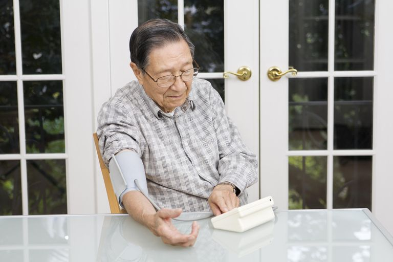 A senior man checks his blood pressure.