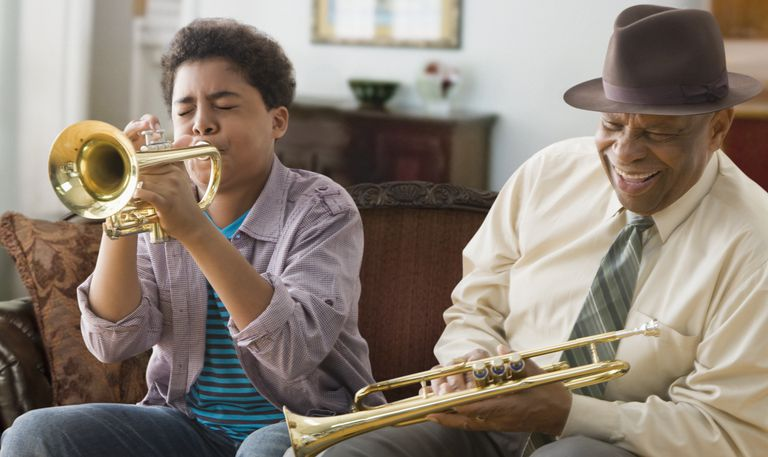 Grandson and grandfather playing trumpet together