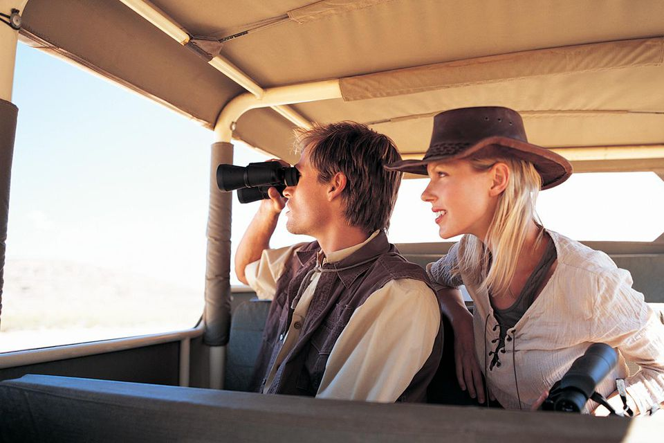 Young Couple on a Safari Travelling in a Jeep Holding and Looking Through Binoculars