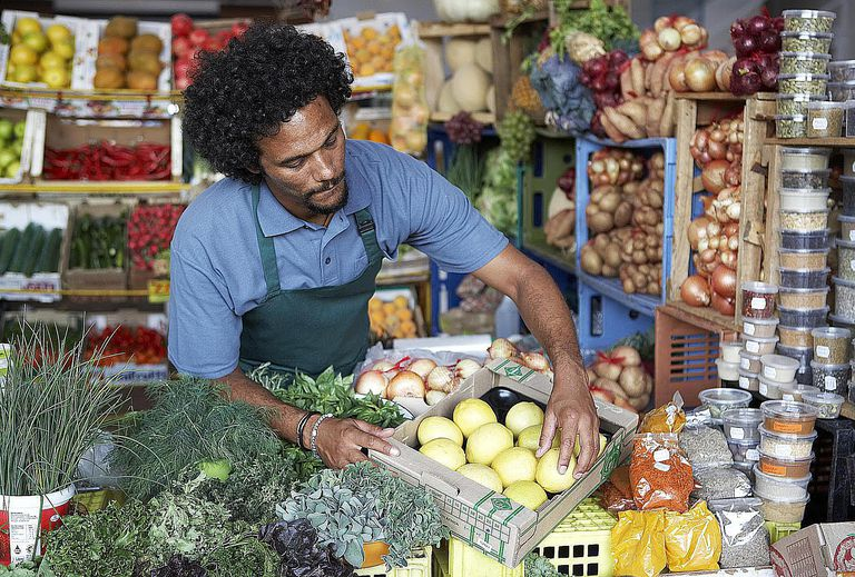 Man working in vegetable market Mixed race...