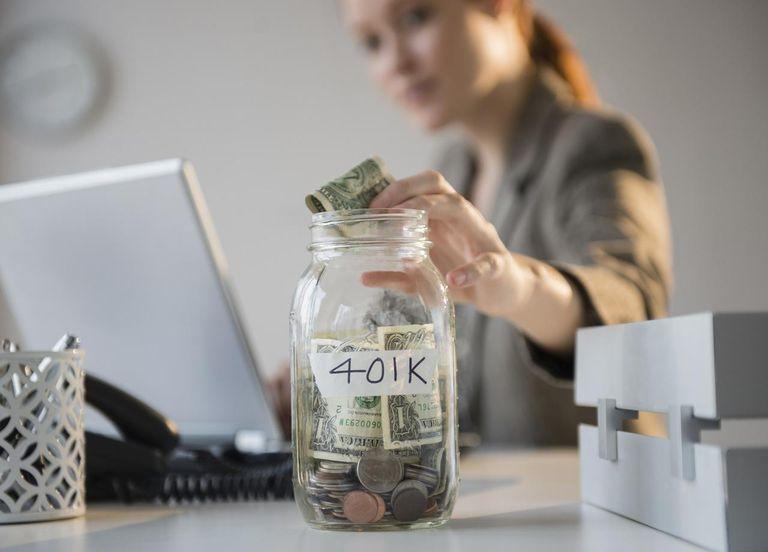 Businesswoman putting money into 401(k) jar at desk.