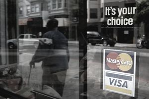 A window sticker advertising Visa and MasterCard credit cards hangs in a window