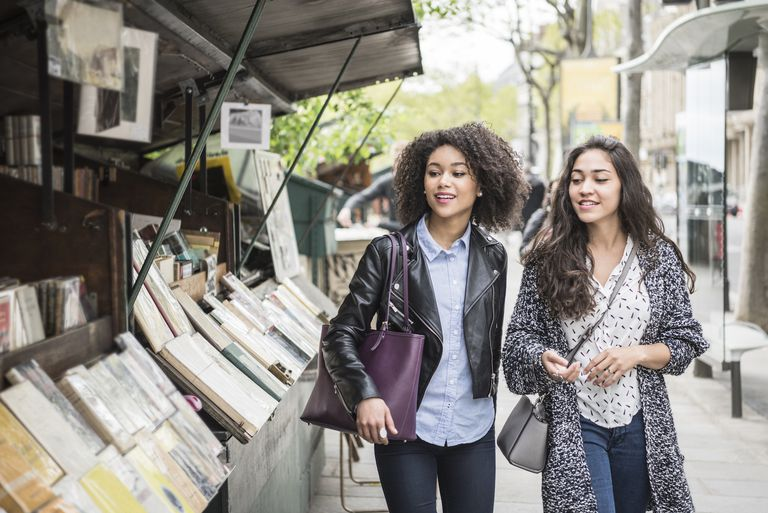 Two female friends walking past bookshop