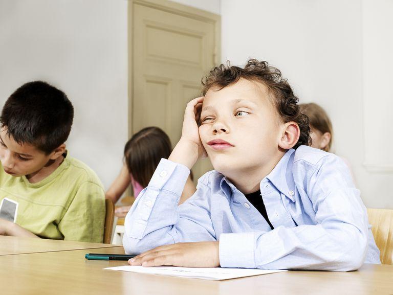 A boy sitting in class, head in hands.