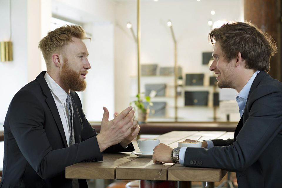 Two young businessmen having meeting in cafe