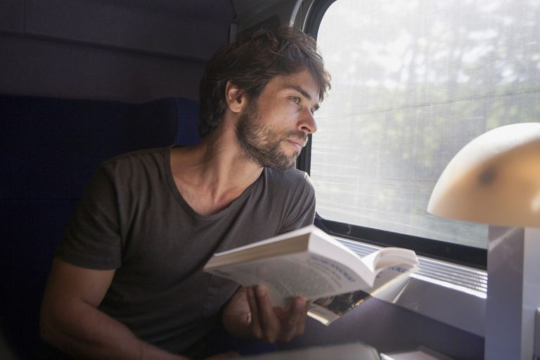 Man sitting on a train with a book