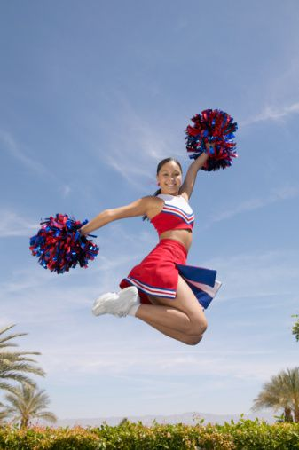 Cheerleader Holding Pompoms Jumps in the Air