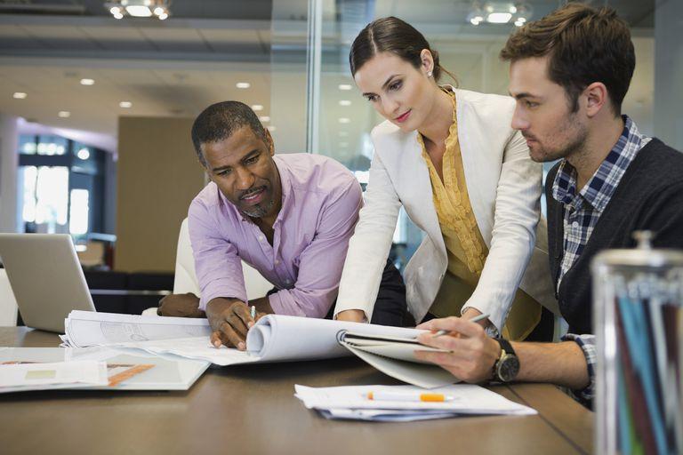 Business colleagues reviewing blueprints