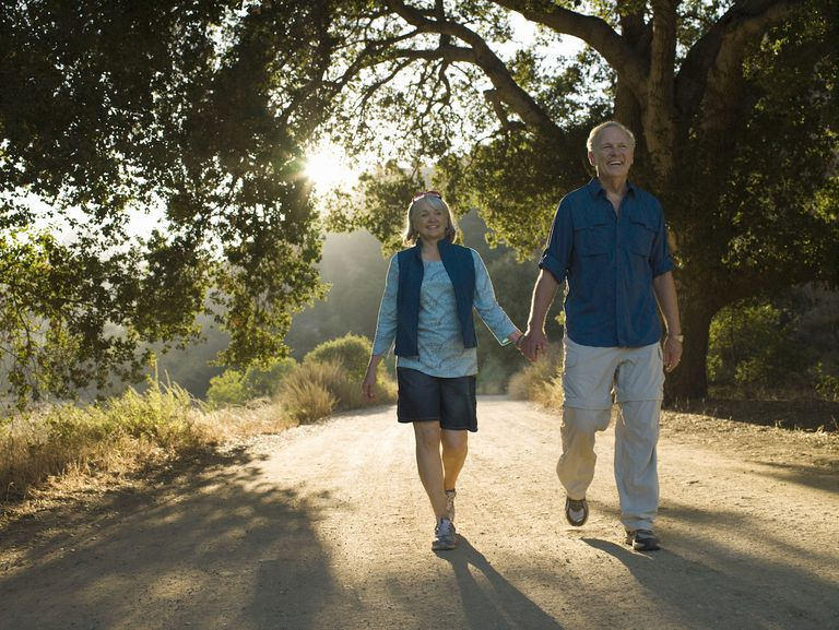 Mature couple walking down dirt road