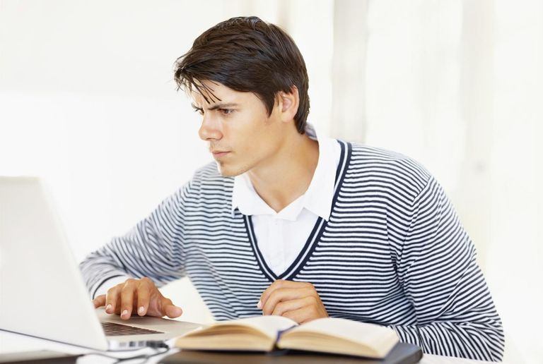 Young male student sitting with a laptop and studying