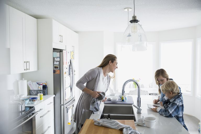Mother drying dishes watching children using digital tablet