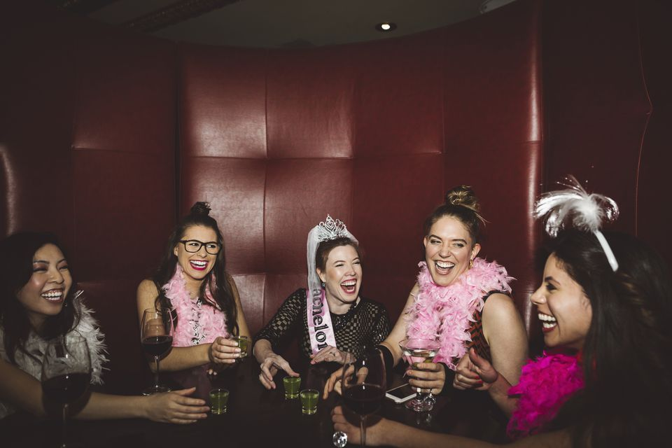 Playful, carefree young female millennial friends drinking, enjoying bachelorette party at nightclub