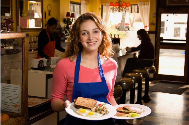 Teenage waitress (16-18) holding plates of food, smiling, portrait