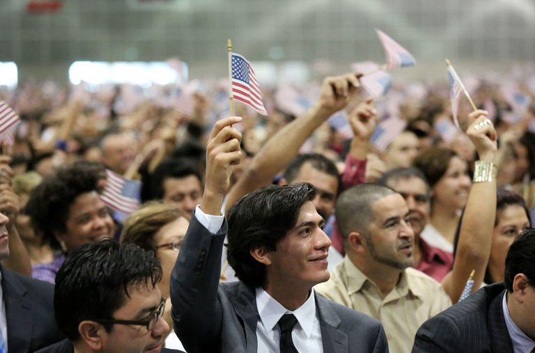Immigrants being sworn in as US citizens represent the process of acculturation.