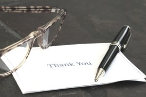 A thank you card with a pen resting on top