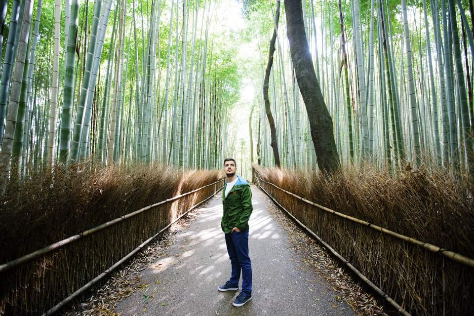 Young man exploring Arashiyama bamboo grove in Kyoto, Japan