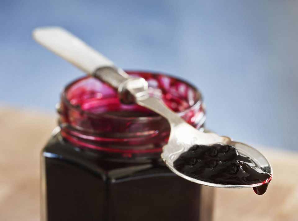 Mulberry jam on a spoon and in jar, close-up