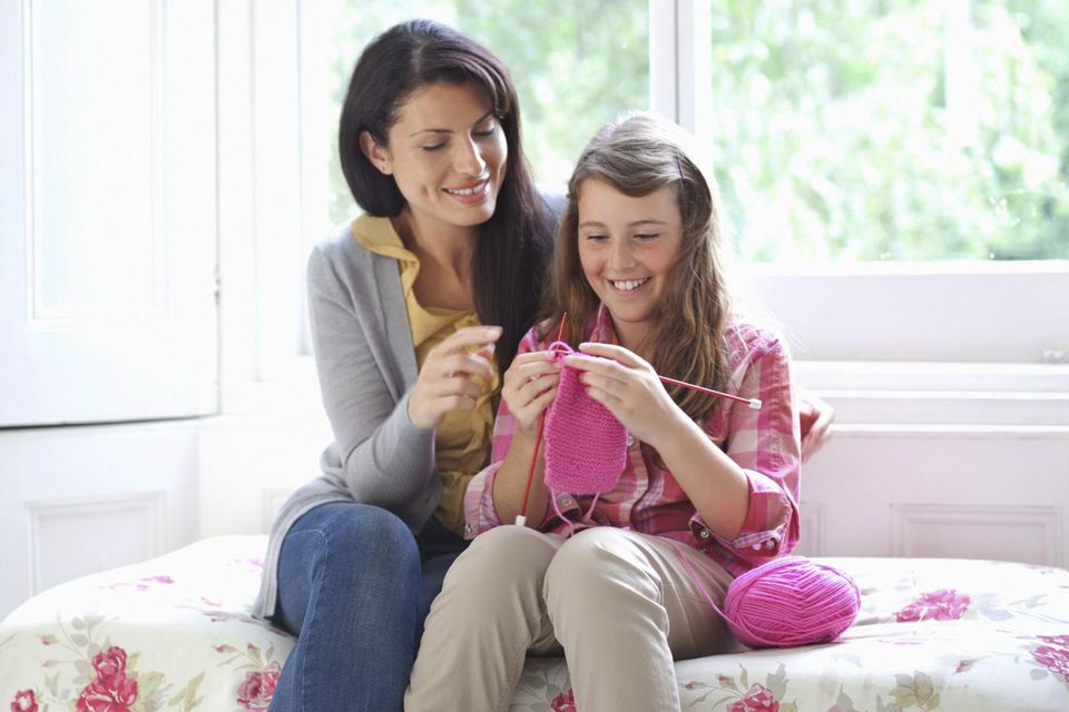 Mother helping daughter (10-11) with knitting