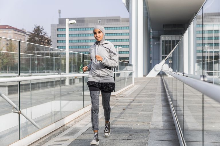 Young muslim woman running in the city