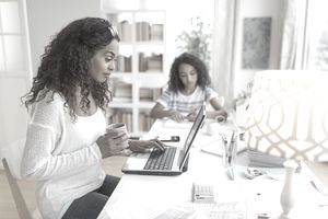 Woman reviewing investments in life insurance with daughter in background