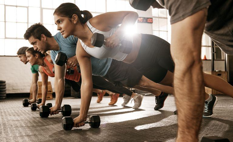 group of people in plank position doing rows with dumbells