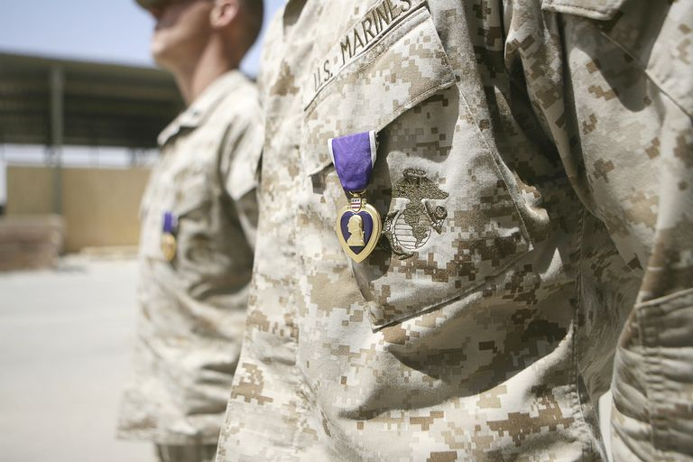 Machine gunners with Security Platoon, Combat Logistics Company 117, Combat Logistics Battalion 7, 1st Marine Logistics Group (Fwd), stand at the position of attention with their Purple Heart awards.