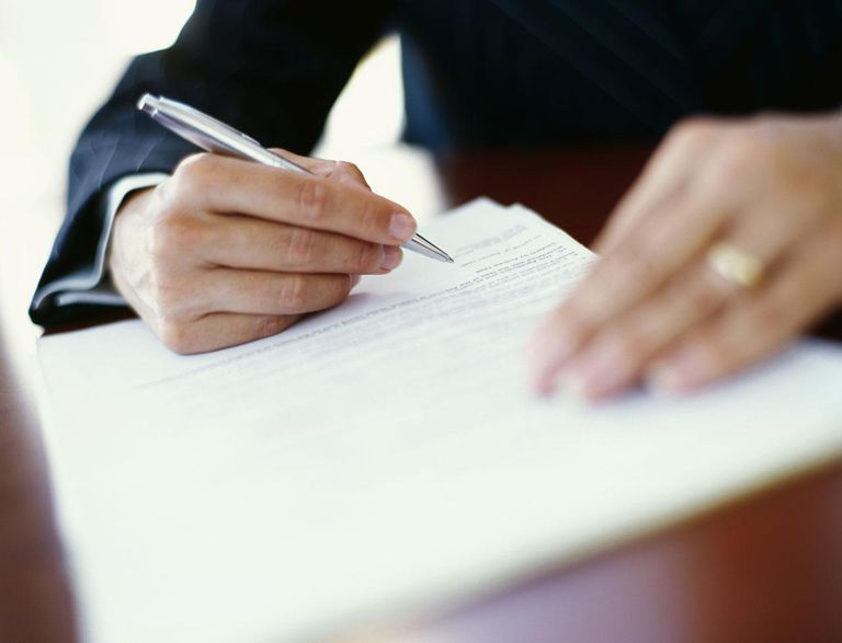 Close-up of a human hand writing on a document in an office