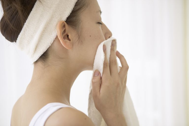 The woman who wipes the face which washed its face with a face towel