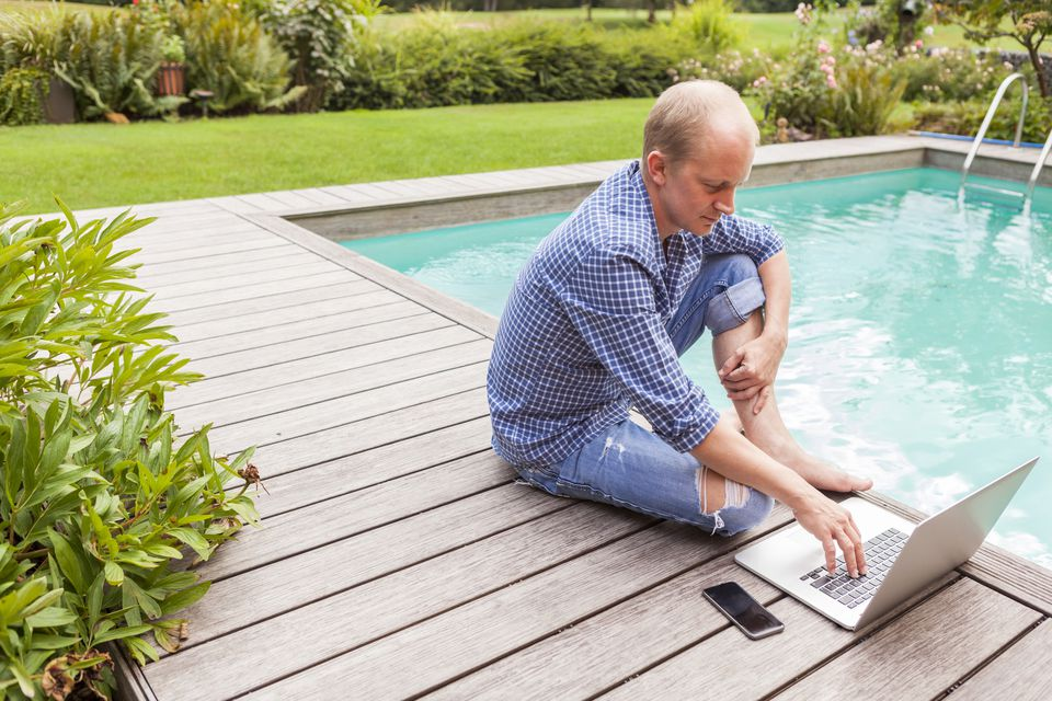 man on computer by pool