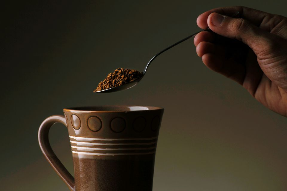 Cropped Person Holding Spoon Of Ground Coffee Against Gray Background