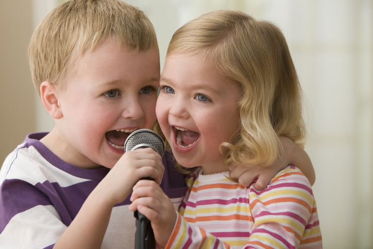 Caucasian brother and sister singing into microphone
