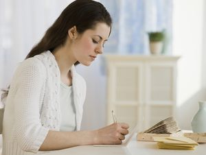 woman writing handwritten note at desk