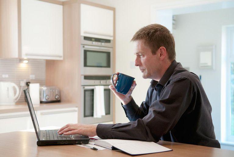 Businessman working on laptop in kitchen