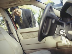 Businessman looking through window at keys locked in car