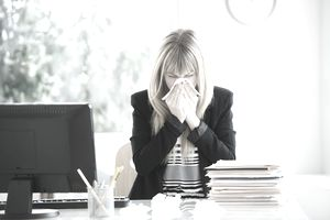 Businesswoman blowing nose in office