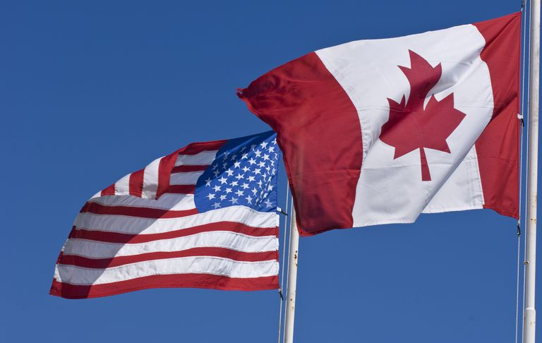 Canadian and United States flags on blue sky