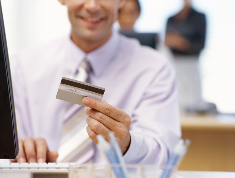 Businessman typing credit card number for online shopping