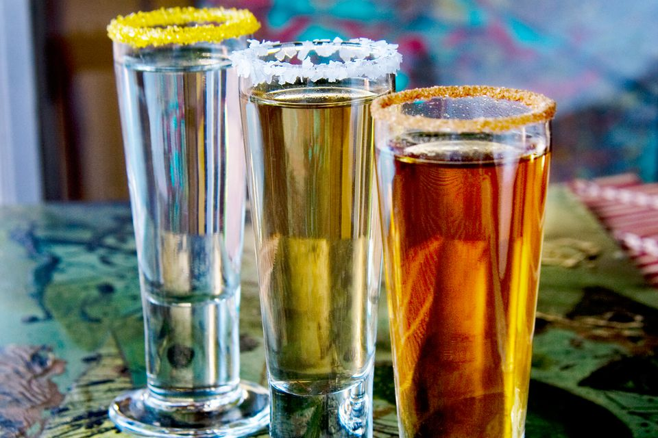 A trio of tequila shots with sugar and salt rims