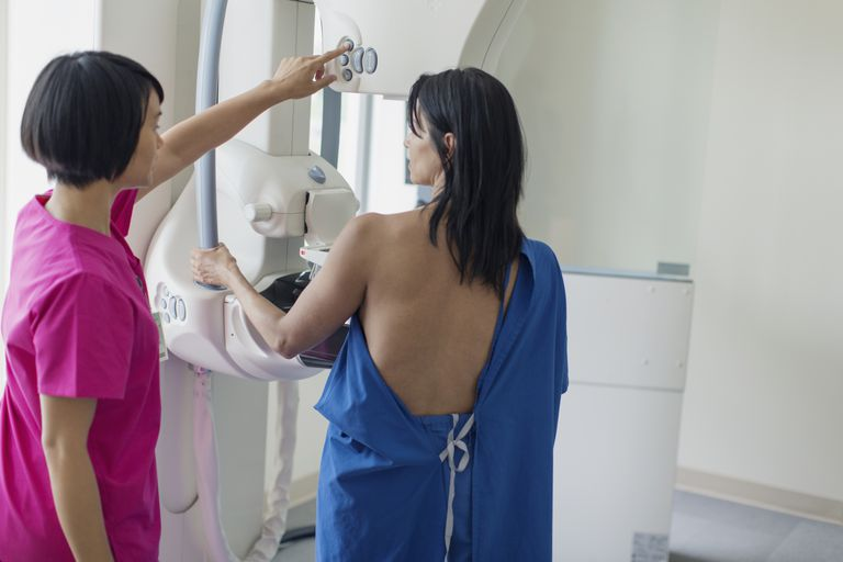 Technician adjusting mammograph machine