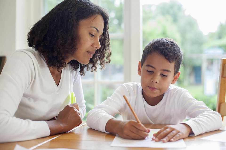 mother helping son with writing assignment