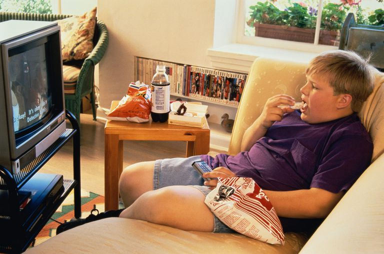 A photo of a boy eating potato chips while watching TV.
