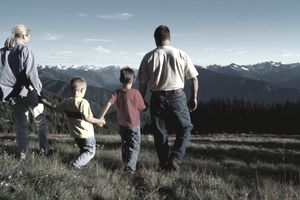 Picture of a family walking outdoors with mountains in the background