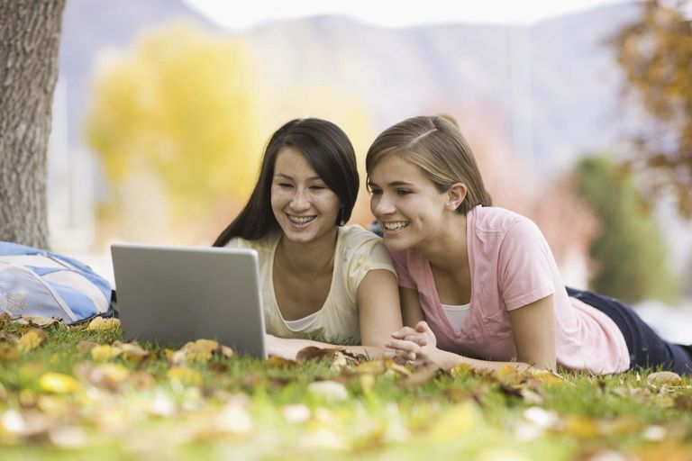 Teenage girls using laptop outdoors